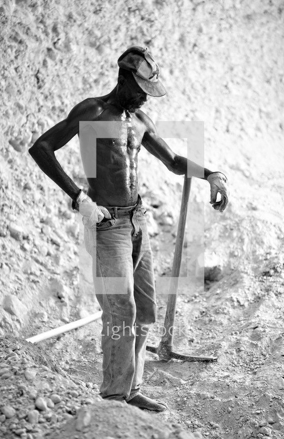 Sweating man holding a trench digger