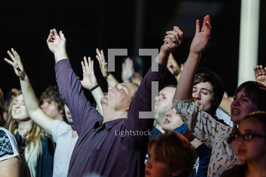 Group praising God hands lifted raised worship