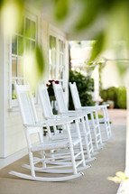 Four white rocking chairs sitting on front porch.
