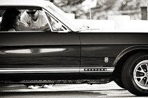 man leaning through a 1966 ford mustang  car window talking to a woman romance love