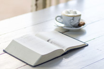 open Bible on a wood floor and coffee cup
