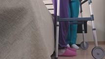 nurse helping a patient use a walker