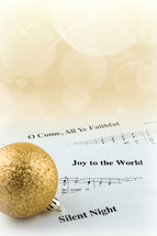 A gold Christmas ball on pages of sheet music of Christmas carols.