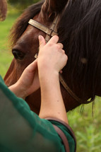 a woman adjusting reins on a horse