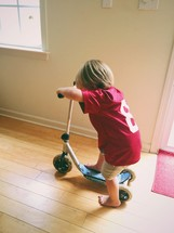 A small boy playing indoors on a small scooter.