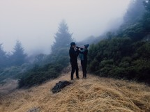 man and woman standing on a foggy mountain top
