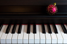 a Christmas ornament on a piano