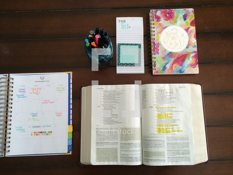 calendar, open Bible, journal, jar of pens, and notepad on a table