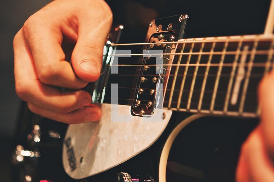 Man's hands strumming guitar.