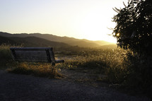 sunrise over a bench looking out at a mountain view