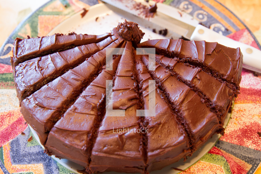 A chocolate caked in slices on a colorful late.