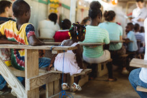 children sitting in desks in a classroom in Haiti