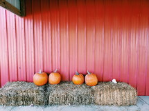 pumpkins on hay bales in front of a red barn