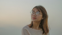 face of a young woman in glasses