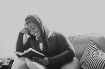 Woman sitting on the sofa reading the Bible.