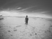 a man standing knee deep in ocean water