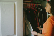 A young woman looking in the closet at clothing
