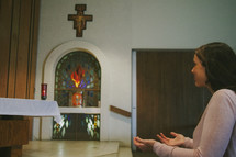 A young woman kneeling and praying in a Catholic church
