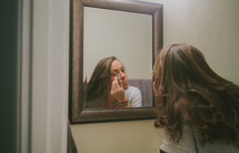 A young woman putting on makeup in the mirror