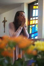 A  joyful young woman kneeling in prayer at a Catholic church