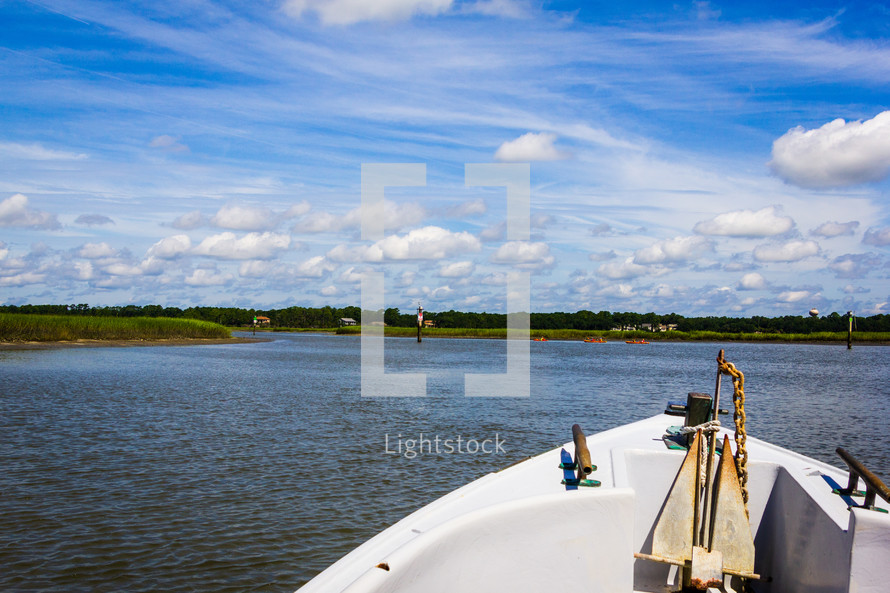 View over the bow of a boat as it travels along a river.