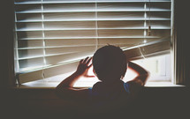a child lifting window blinds and  looking through a window