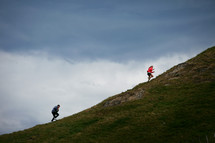 man and woman running up a mountain
