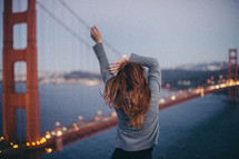 a woman stretching in front of the golden gate bridge
