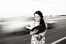 woman reading a Bible in front of speeding cars on a highway