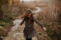 girl in a dress running on a path