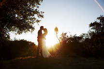 couple kissing outdoors under the glow of sunlight
