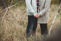 a couple holding hands standing in a field