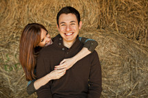 woman with her arms around a man in a hay stack