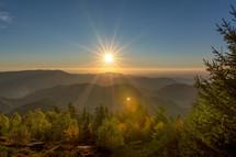 sunburst over black forest in autumn