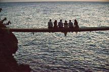 bridal party sitting on a pier