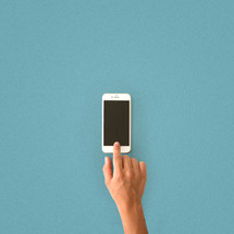 A person's finger on a white cell phone laying on a blue surface.