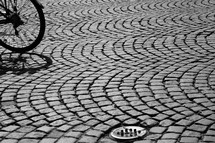Bicycle wheel on arched cobblestone street.