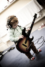toddler boy with headphones and a guitar