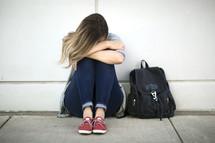 sad girl sitting next to a book bag