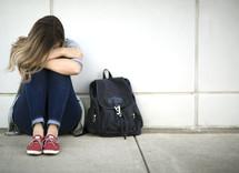 sad girl next to a book bag