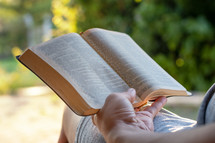 person reading a Bible in a chair outdoors