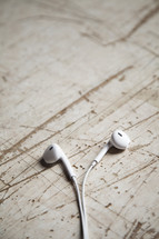 earbuds on scratched wood