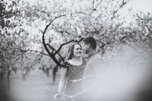 happy couple standing in an orchard