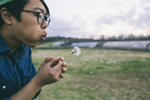 Girl blowing a dandelion flower in a field
