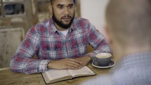 two men having a conversation over coffee and discussing scripture