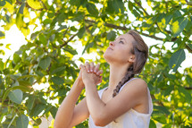 a woman looking up and praying
