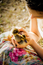 a woman holding ducklings