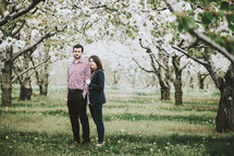 a couple standing in an orchard in spring