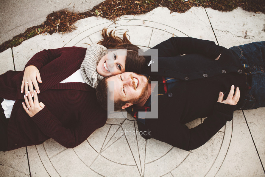 a couple lying on the sidewalk looking up at the camera