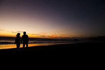 silhouette of a couple walking holding hands on the beach love relationship marriage